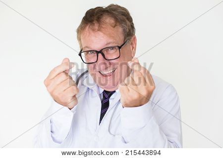 Closeup portrait of happy middle-aged male doctor looking at camera, showing money gesture and asking for money. Isolated front view on white background.