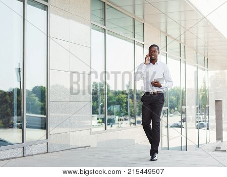 Happy black businessman talking on smartphone, walking along city center with tablet in hand. Young african-american successful man having friendly conversation outdoors in urban cityscape