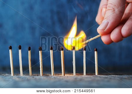 matches in a row on a wooden background, a hand with a burning match sets fire to another match.
