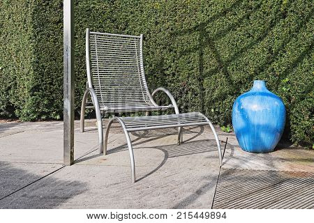 Modern garden chair with footstool and decorative blue vase with a coniferous hedge in the background.