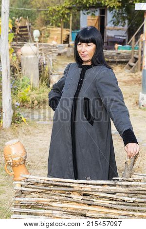 Smiling woman with black hair in ancient national clothes stands near the fence against the backdrop of rural farmstead. Ukrainian village.
