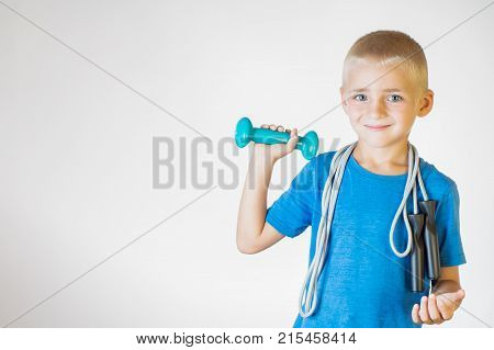 Boy with skipping rope and dumbbell. Portrait happy smiling boy holding a jump rope and dumbbell. The concept of a healthy lifestyle sport or workout.