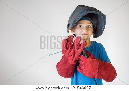 Happy little kid in welder mask and welding equipment. Welding equipment welding mask protective leather gloves welding electrodes. Fun concept. Child dreaming of future profession. Career choice.