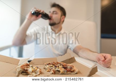 A man drinks a bottle after drinking a fast food. Drink after pizza. Focus on pizza.