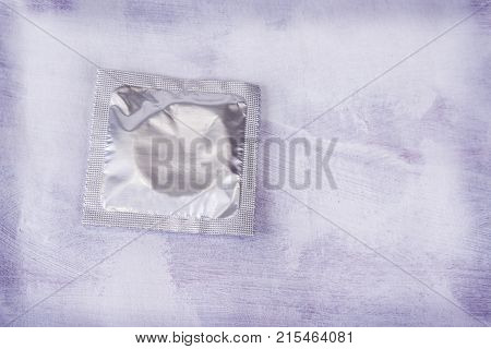 Safe sex concept. Condom on light grungy background