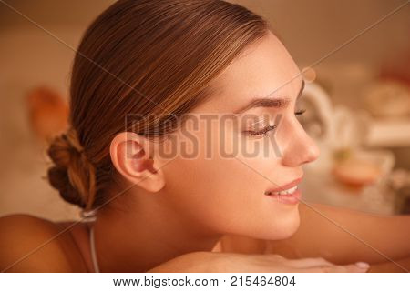 Close up profile of relaxed young woman enjoying pampering water in bath. She is smiling with happiness