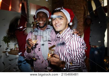 Intercultural guys with champagne and their friends enjoying dances on background