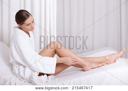 My legs are so smooth after spa treatment. Calm young woman is touching skin of her leg with satisfaction. She is sitting on deckchair in bathrobe