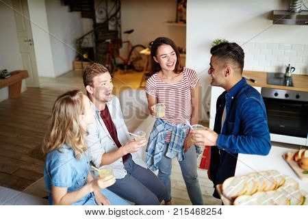 Joyful friends talking by drink while gathering at home after work