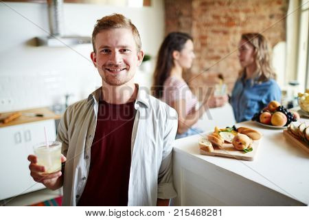 Young man with drink standing by festive table while two girls talking on background