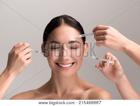 Enjoying care of my skin. Portrait of happy young woman is standing with closed eyes and smiling while hands with syringes are injecting filler into her face. Isolated background