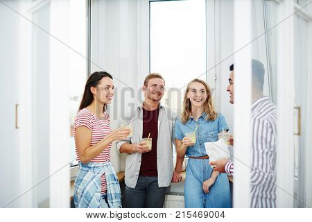 Friendly guys and girls with drinks standing by window and discussing funny things