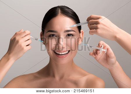 Perfect skin again. Portrait of naked asian lady is trusting her face to specialist who is performing cosmetic treatment. She is looking at camera with joy while having injections of botox. Isolated