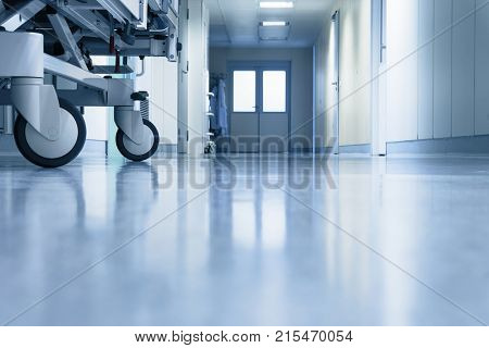 An interior of a hospital hallway with a stretchers wheels