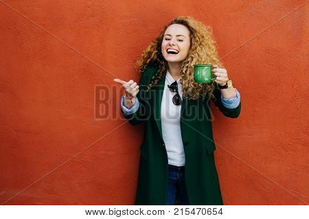 Excited Woman With Curly Blonde Hair Wearing Jacket Holding Green Cup Of Coffee Raising Her Thumb Sh