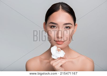 Tender skincare. Portrait of wistful young naked asian woman is looking at camera thoughtfully while touching her chin by white orchid. Isolated background. Beauty of skin concept