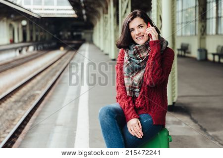 Beautiful Brunette Female Wears Knitted Sweater And Scarf, Sits On Suitcase Near Platform, Communica