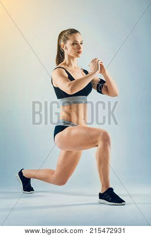 Say no to a passive lifestyle. Muscular female athlete listening to the motivating music and focusing on her training session while doing a lunging exercise alone.