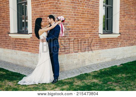 Horizontal Portrait Of Romantic Bride And Bridegroom Embrace As Stand Outdoor Near Ancient Builduing