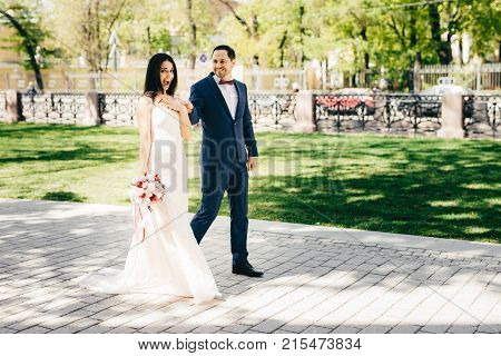 Emotional Female Bride In White Long Dress Holds Wedding Bouquet Has Walk Together With Male Bridegr