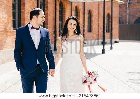 Positive Female Brunette In White Wedding Dress, Holds Bouquet And Bridegroom`s Hand, Celebrate Thei