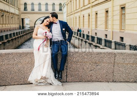 Affectionate Married Couple Sit On Bridge Togetherm Enjoy Fresh Air, Have Good Relationship, Kiss Ea