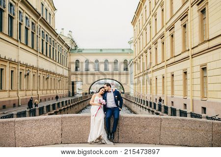 Portrait Of Handsome Bridegroom And Bride Embrace Each Other, Sit On Ancient Bridge, Enjoy Calmlenes