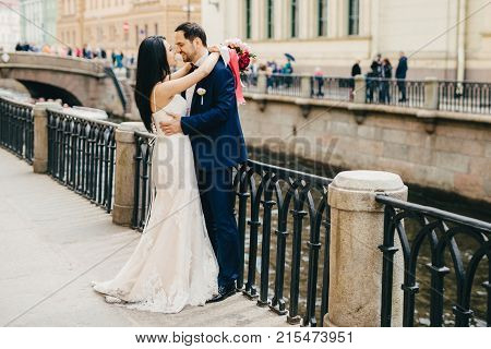 Brunette Female In White Dress Embraces Her Bridegroom, Looks With Great Love At His Eyes, Stand Tog