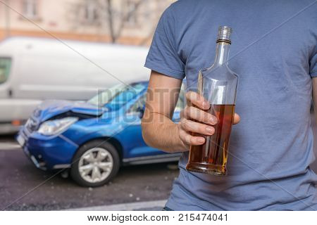 Traffic accident and alcohol concept. Drunk driver is holding bottle with alcohol in hand. Crashed car in background.