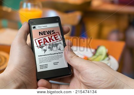 Man Is Holding Smartphone And Reading Fake News On Internet. Pro