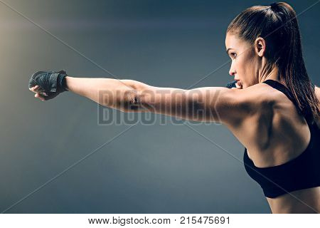 The toughest sport in the world. Waist up shot of a young muscular female boxer having a well trained body punching while training alone over the dark background.