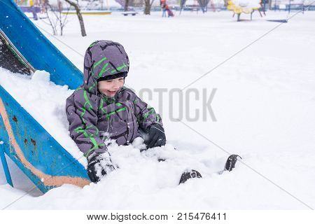 Little boy having fun in the snow. after snowfall. active winter leasure time outdoors