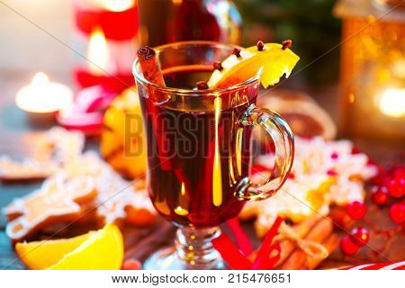 Mulled Wine. Traditional Christmas Mulled Wine hot drink with cinnamon stick, slices of orange and spices, on holiday decorated Christmas table. Christmas dinner