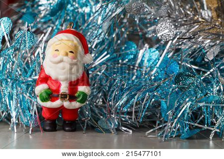 Santa Claus figurine and blue and silvery tinsel as decoration for Christmas