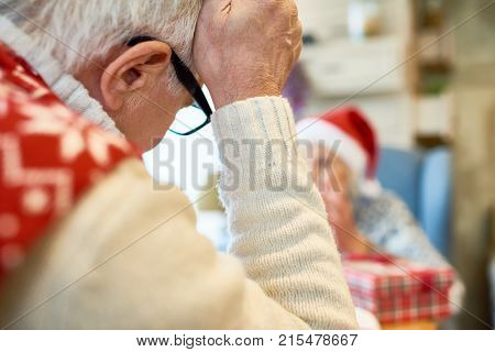 Back view of senior man leaning head on hand pensively while sitting at dinner table during Christmas holidays, copy space