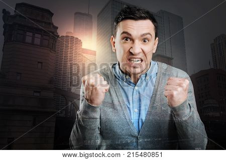 Stop doing that. Furious young man cannot keep his emotions inside and showing his fists after having a nervous breakdown.