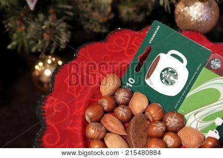 Camberley UK - December 31 2016: Starbucks coffee gift card on a festive Christmas plate of mixed nuts
