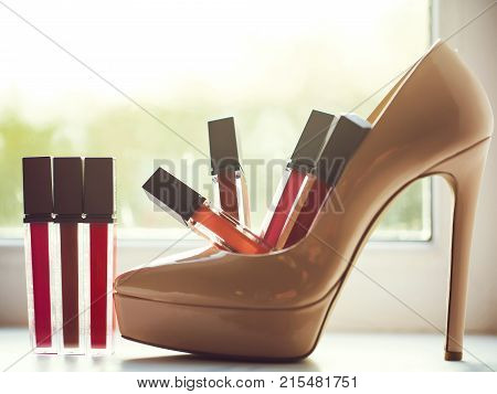 Colorful lip gloss cylindrical bottles decorative makeup in beige high heel shoe on window sill