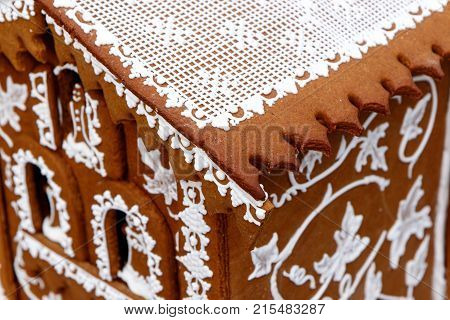 Ornate gingerbread house with decorative white frosting and ginger bread man and woman figurines