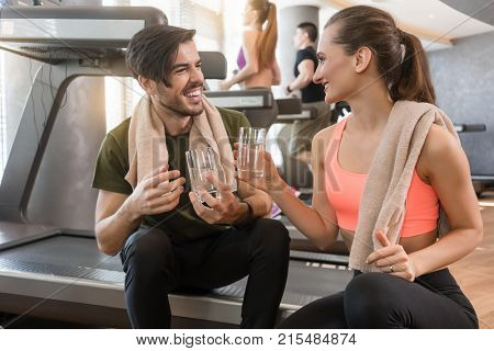Cheerful young man and woman with a healthy lifestyle drinking plain water for hydration during break at the fitness club