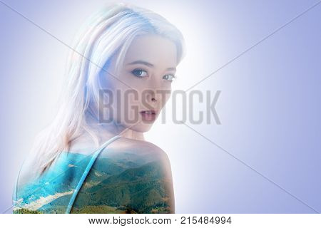 Magnetic look. Pretty nice young woman sitting and looking at you while dreaming about the mountains