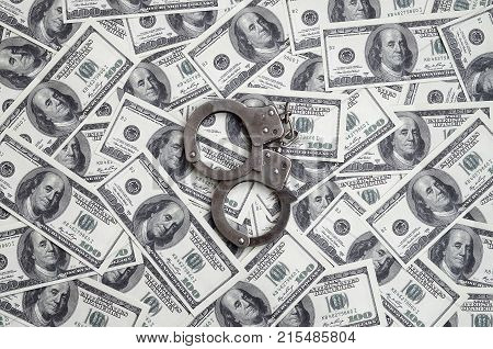 Police Handcuffs Lie On A Lot Of Dollar Bills. The Concept Of Illegal Possession Of Money, Illegal T
