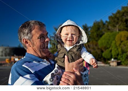 Portrait of a happy grandfather holding his grandson in his hands