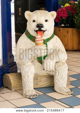 EASTBOURNE, UK - SEPTEMBER 19, 2016: Model statue of a polar bear licking an ice cream cone on the pier at Eastbourne, UK
