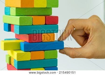 Hand pulling colorful wooden block from the tower as Business Risk or stability concept.