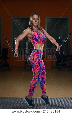 Beautiful slim young sportswoman in colored gymnastic costume and sneakers posing holding the handles of the simulator in the gym