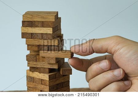 Risk or stability concept as hand pulling wooden block from the tower.