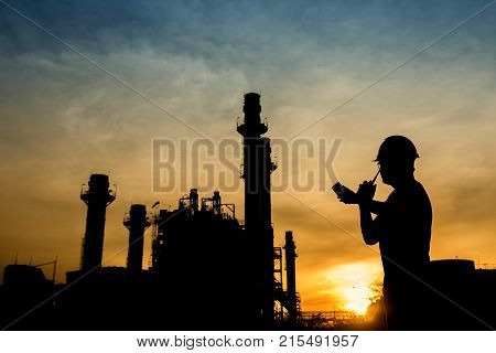 Silhouette Engineer Is Recording Data Against Combine Cycle Power Plant Background