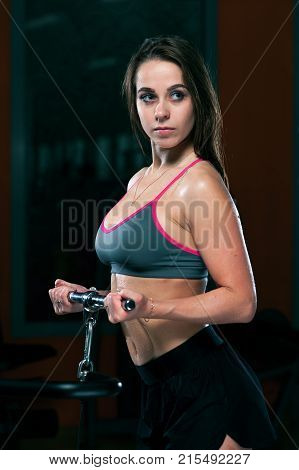 Beautiful slim muscular young woman in sportswear doing exercises on the simulator in the gym