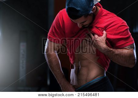 Cute young sports man in red t-shirt shows relief abdominal muscles in gym. Panoramic shot.